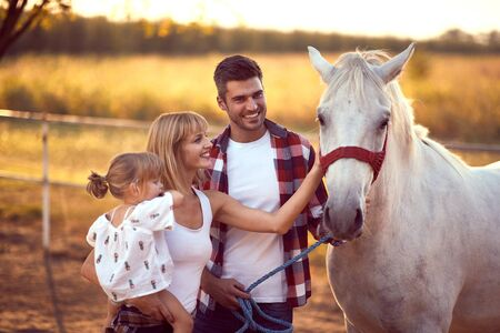 Happy family petting a white horse, enjoying the outdoors. Fun on countryside, sunset golden hour. Freedom nature concept.