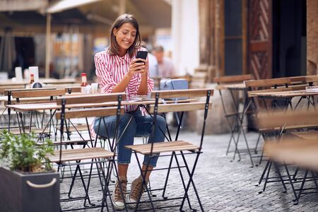 Young girl  using phone and drinking coffee in cafe.