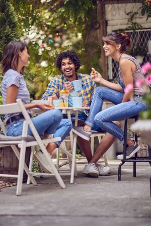 group of smiling  young friends  talking outdoor in nature  while having a coffee time.