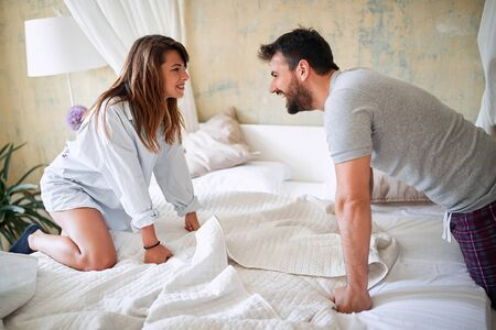 young sexy couple in underwear having a foreplay in bed in the bright morning on valentine's day. Intimacy, passion, erotic concept.