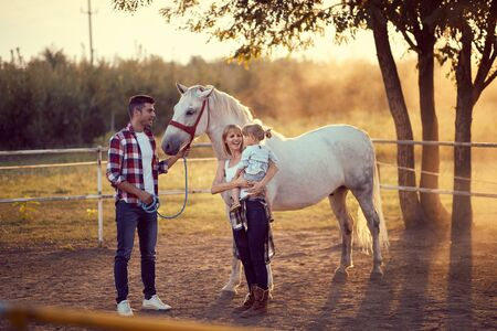 Happy family on the horse ranch petting a horse. Young happy family having fun at countryside outdoors. Sunset, golden hour