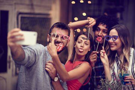 smiling group of  friends having fun with props on stick in nightclub celebrating. Party, Celebration, togetherness, socializing concept.