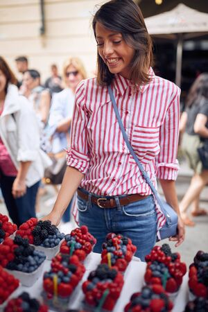 Happy woman traveler buying fresh fruit on food market at street Zdjęcie Seryjne