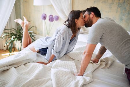 young sexy couple in underwear having a kiss in bed in the bright morning on valentine's day. Intimacy, passion, erotic concept.