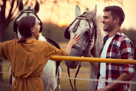 Happy couple having fun on the horse ranch, people in love. Fun on countryside, sunset golden hour. Freedom nature concept. Zdjęcie Seryjne
