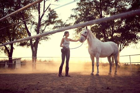 Woman holding a helmet and petting a horse on the ranch. Training on countryside, sunset golden hour. Freedom nature concept.