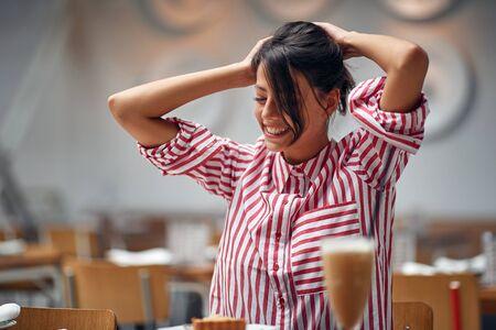 Smiling woman sitting at cafe and enjoying it free time alone. Zdjęcie Seryjne