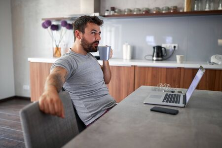 adult young male with beard sitting and drinking coffee in front of laptop on table. modern lifestyle, relaxed, business concept