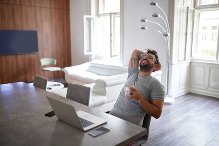 Young handsome man with beard and glasses, smiling, sitting, leaned back, relaxing, with laptop on table in front of him and two cell phones. casual business concept