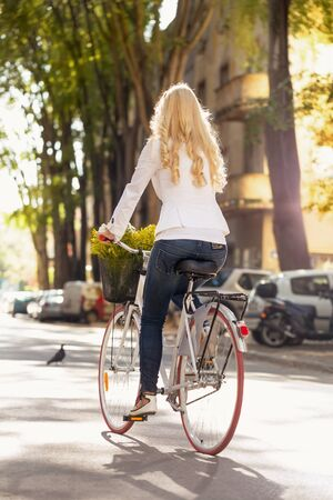 Urban leisure - young woman and bike in city, back view