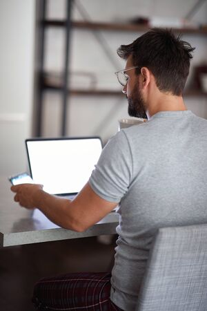 adult young man with beard wearing glasses,  watching his cell phone in front of laptop on table. technology,  lifestyle, freelance, social media concept