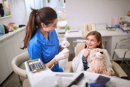 Smiling girl in dental chair showing tooth to dentist