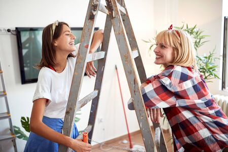 Two female friends laughing and smiling watching at each other in apartment leaned on a ladder.