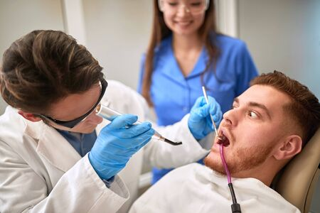 Scared male patient at dentist repairing tooth Stock Photo