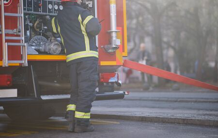 Fireman in uniform in front of fire truck going to rescue and protect. Emergancy , danger, servise concept.