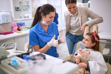 Happy female dentist raised thumbs to little patient