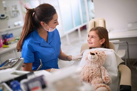 Young female dentist relaxes girl in dental chair
