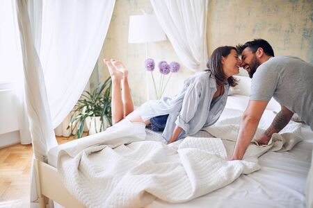 Happy woman and man enjoying intimate moment at morning in bed. Reklamní fotografie