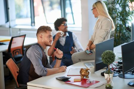 young business man watching content on monitor in the office, comparing data with the ones on the paper in front of him. colleagues in the background having casual talk