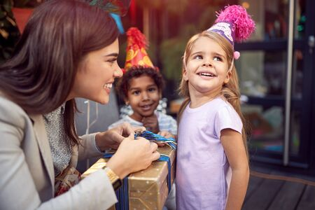 A female brunette opening  birthday presents to a little girl looking away, smiling