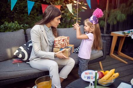 Young female brunette holding birthday present and talking to a sweet little girl.