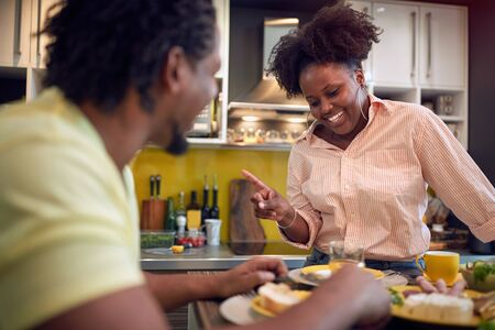 A afro-american couple having an interesting conversation in the kitchen at the table