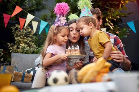 A family blowing birthday candles together. Foto de archivo