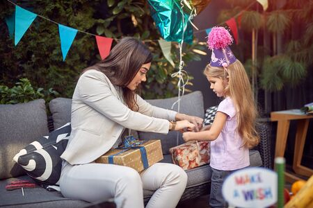 A female  opening  birthday presents with sweet little girl.