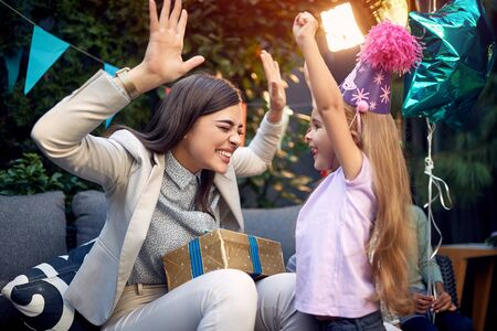 Young adult female with arms up holding present for a little girl at birthday