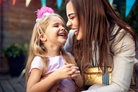 A little girl giggling in a hug of a young female adult  birthday party.