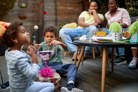 afro-american kids playing on a birthday party with their parents sitting in the background. Family concept
