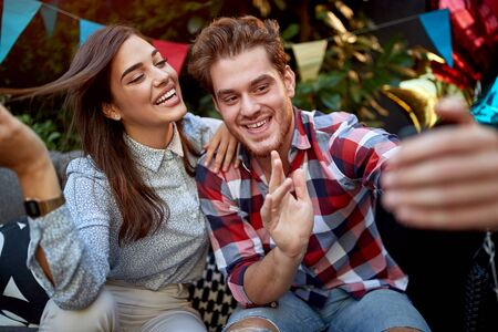 young adult couple taking selfie on a party, posing