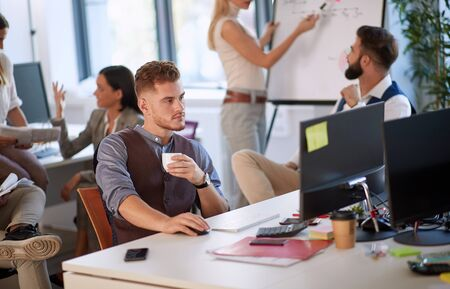 Young entrepreneur holding a coffee cup while sitting and working in the office full of people