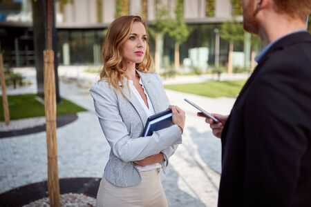 young caucasian businesswoman looking interested to her interlocutor outdoor in front of business building. outdoor, unofficial, meeting, sharing information, selling, making deal 스톡 콘텐츠