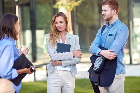 close up of young female business woman talking to a two colleagues in front of a building.