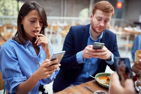people at lunch in their worlds, distracted from each other by cell phones. not present, social issues, victims of modern technology