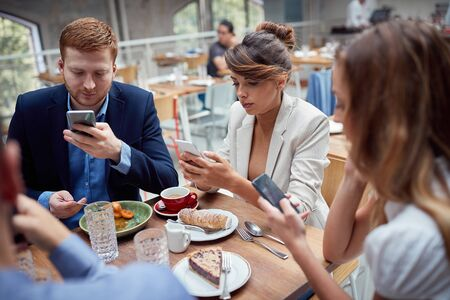 young caucasian people having unsocial lunch in restaurant, using their cell phones and not talking to each other. social issues, victims of modern technology Фото со стока