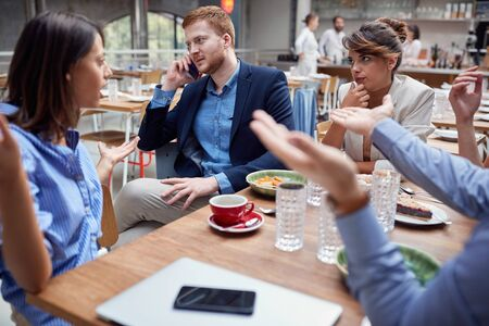 group of young caucasian people talking  at lunch. friends, colleagues, business partners concept Фото со стока