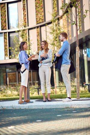 young female business woman talking to a two caucasian colleagues in front of a building.