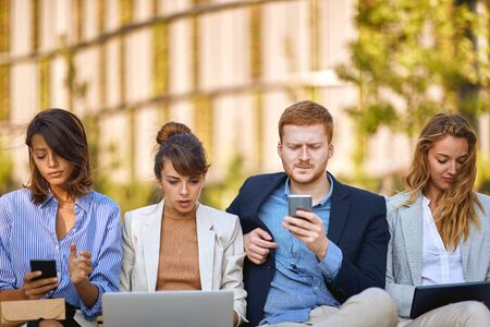 worried businesspeople sitting outdoor, working on laptop and cell phones. business after corona virus, bad economy, issues, recession concept Фото со стока
