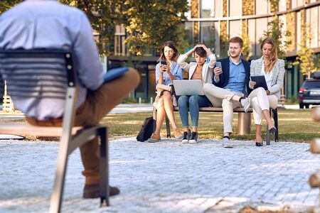 worried businesspeople sitting outdoor in park at bench, working on laptop, cell phones, tablet. business after corona virus, bad economy, issues, recession concept