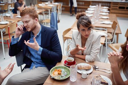 young adult businesspeople at lunch in a restaurant discussing about issues after coronavirus. covid 19, recesion, economy, business problems concept Фото со стока