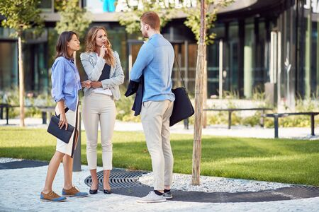 group of young business people talking in front of a building. two female and one male colleague 스톡 콘텐츠