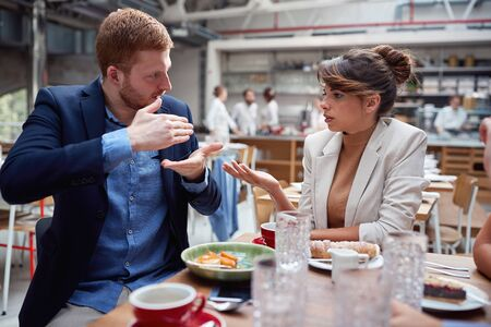 man and woman discussing at lunch. friends, colleagues, couple, business partners concept Фото со стока