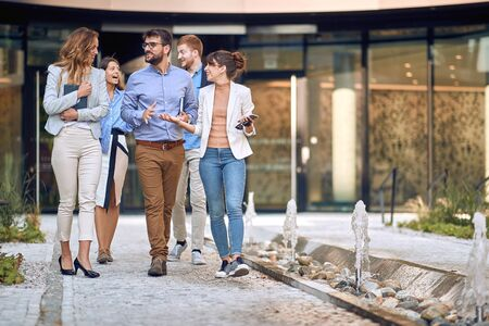 group of young businesspeople walking out of the building to have a break. leaving meeting. Фото со стока