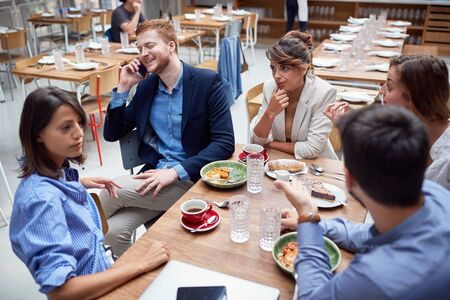 group of young caucasian people discussing at lunch. friends, colleagues, business partners concept