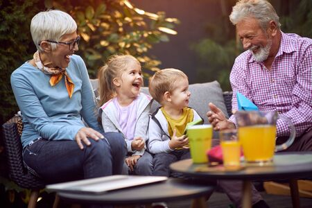Cheerful kids spending good and funny time with their happy grandparents.