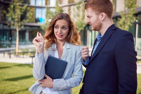 young caucasian businesswoman showing, explaining, to a male colleague, outside, in front of a business building