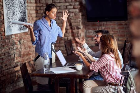 very angry woman yelling with arms spread on a husband in cafe drinking coffee with another young female. rage, conflict, adultery, jealousy concept Foto de archivo