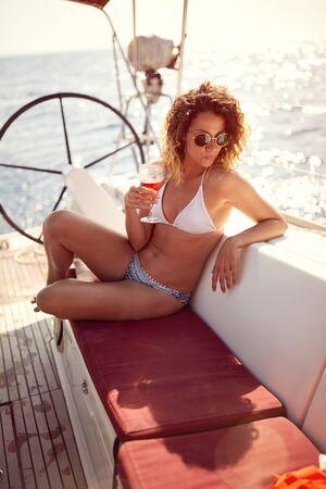 Young girl on yacht sea cruise vacation enjoying at wine. Banque d'images - 149579473